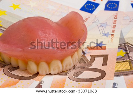 false teeth prosthetic on euro bills with focus on the front teeth - stock photo