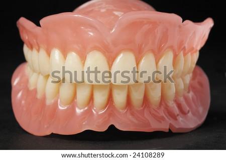 False teeth prosthetic on isolated  black background - stock photo