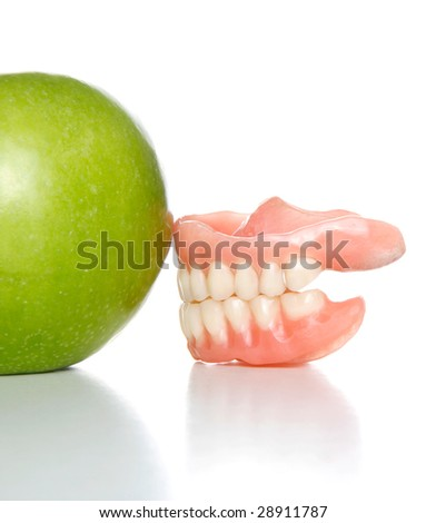 False teeth pushing an apple out of the picture - stock photo