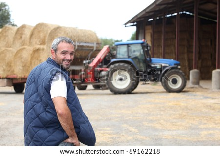 Famer stood by hay barn - stock photo