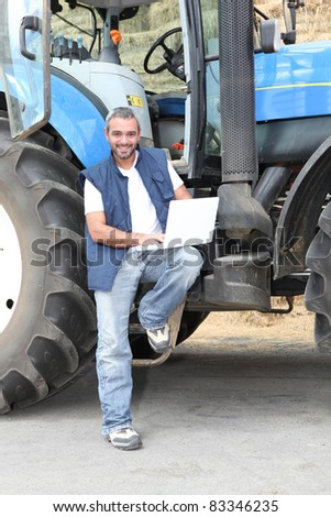 Famer with laptop computer stood by tractor - stock photo