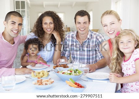 Families Enjoying Meal Together At Home - stock photo