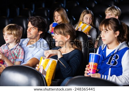 Families having snacks while watching movie in cinema theater - stock photo