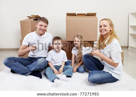 Families with children drinking tea on a background of cardboard boxes - stock photo