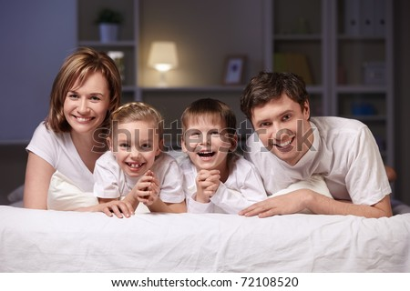 Families with children in bed at night - stock photo