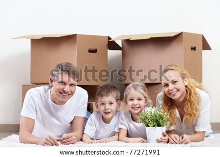 Families with children on the carpet against the backdrop of cardboard boxes - stock photo