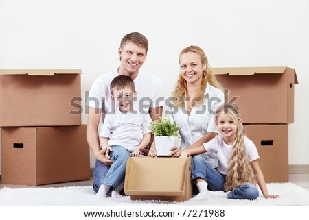 Families with young children unpack boxes - stock photo