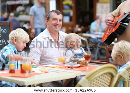 Family, a father with three children, two teenager twins sons and little baby daughter, are listening music in cafe on summer terrace in a center of busy city street, boy is playing with smart phone - stock photo