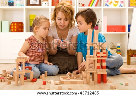 Family activities in the kids room - woman and children sitting on the foor playing - stock photo