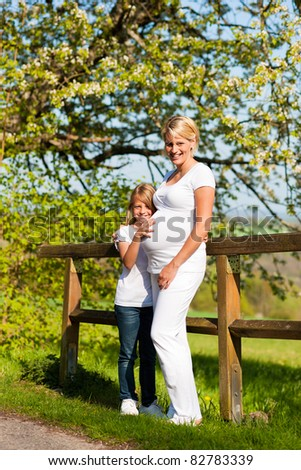 Family affairs - Girl is touching round belly of her pregnant mother in anticipation of the new sibling - stock photo