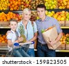 Family against shelves of fruits goes shopping. Father keeps a paper bag with fruits and vegetables, son hands pineapple - stock photo