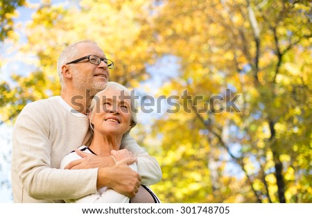 family, age, season and people concept - happy senior couple hugging over autumn trees background - stock photo