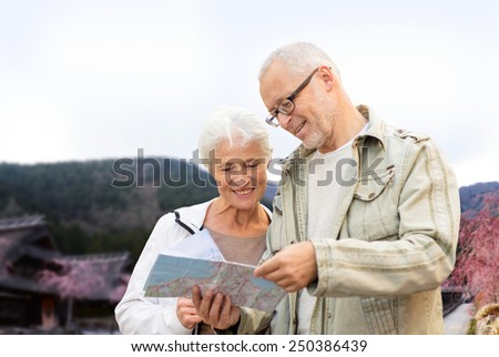 family, age, tourism, travel and people concept - senior couple with map and over asian village and mountains landscape background
