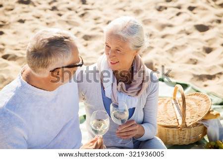 family, age, travel, tourism and people concept - happy senior couple having picnic and talking on summer beach