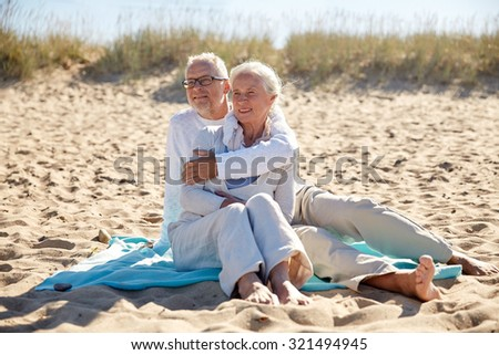family, age, travel, tourism and people concept - happy senior couple sitting on plaid and hugging on summer beach - stock photo