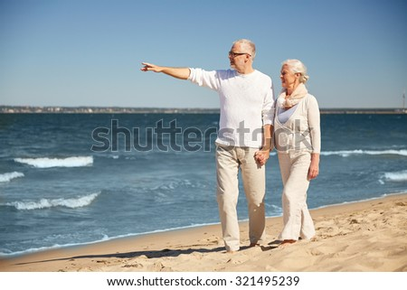 family, age, travel, tourism and people concept - happy senior couple walking and pointing finger to something on summer beach - stock photo