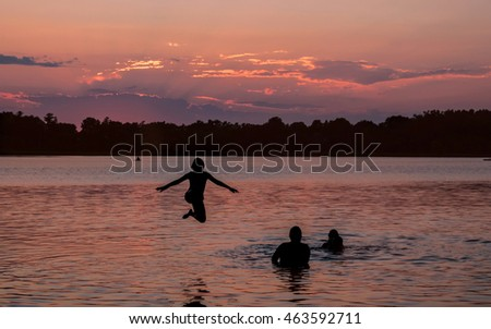 Family and friends are having fun at a lake under sunset