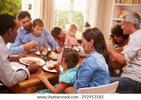 Family and friends sitting at a dining table - stock photo
