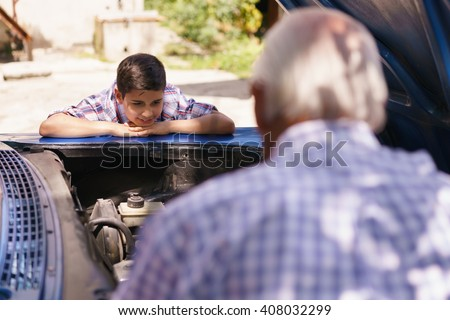 Family and Generation gap. Old grandpa spending time with his grandson. The senior man shows the engine of a vintage car from the 60s to the preteen child. They boy smiles happy. - stock photo
