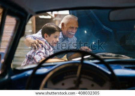 Family and Generation gap. Old grandpa spending time with his grandson. The senior man shows the engine of a vintage car from the 60s to the preteen child. They smile happy.  - stock photo