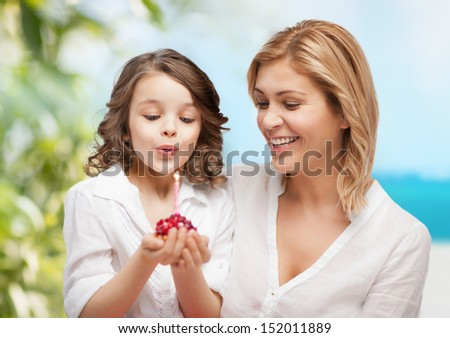 family and holidays concept - happy mother and daughter with birthday cake