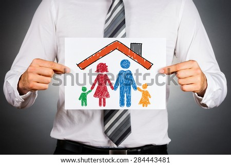 Family and home insurance concept. Colorful drawing of a family under the home roof. - stock photo