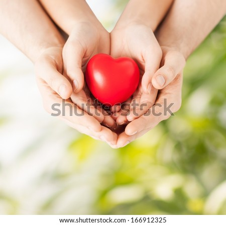 family and love concept - close up of woman and man hands with heart