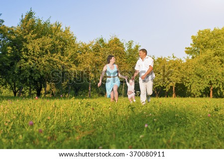 Family and Relationships Concepts. Happy Young Family Running Together Outdoors on Nature. Horizontal Image Orientation - stock photo