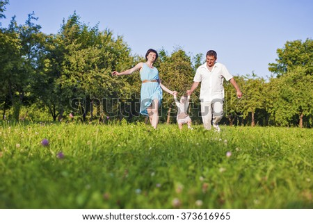 Family and Relationships Concepts. Happy Young Family Spending Time Together Outdoors on Nature. Horizontal Image
