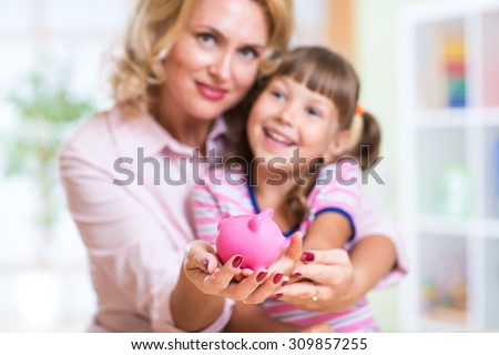 family and savings concept - happy mother and child daughter putting money to piggy bank - stock photo