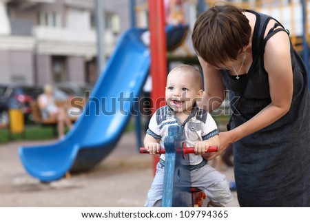 Family and spring toy horse at outdoor playground