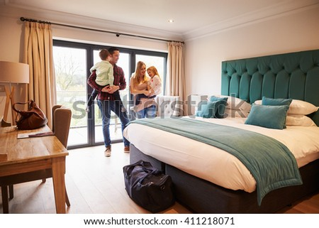 Family Arriving In Hotel Room On Vacation - stock photo