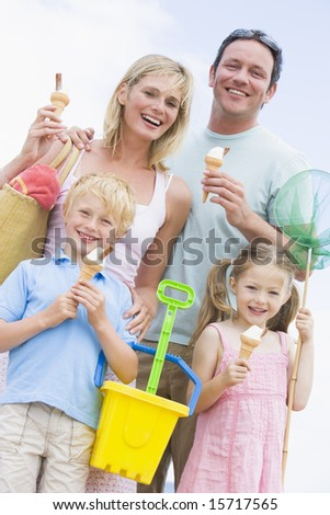 Family at beach with ice cream cones smiling - stock photo