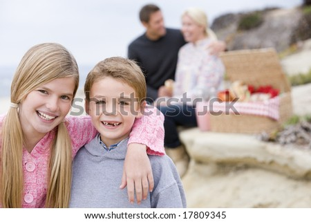 Family at beach with picnic smiling - stock photo