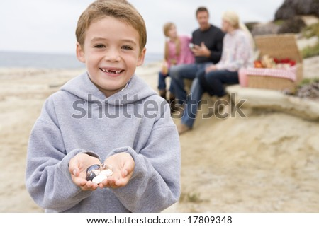 Family at beach with picnic smiling focus on boy with seashells - stock photo