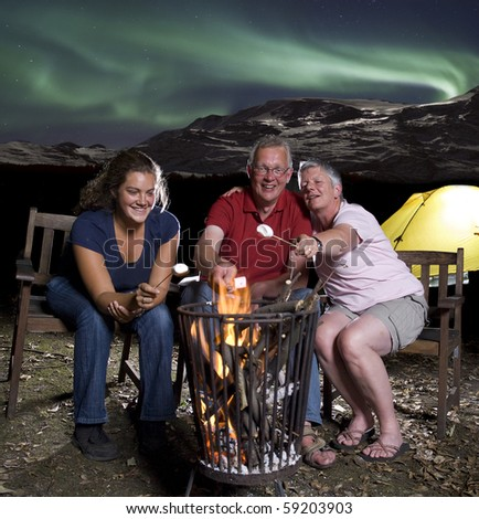 Family at campfire in mountains with northern lights - stock photo