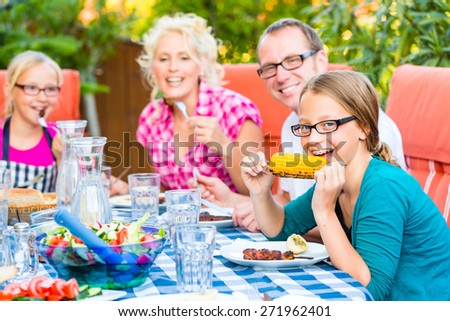 Family at eating in garden summer barbecue - stock photo