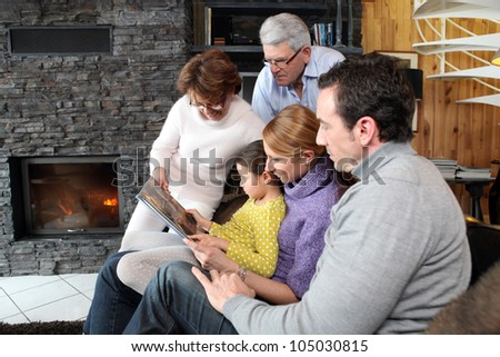 Family at home around a fireplace - stock photo