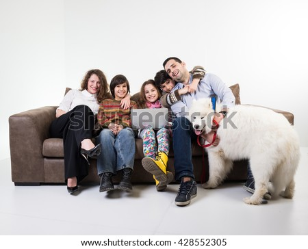 Family at home sitting at sofa - stock photo