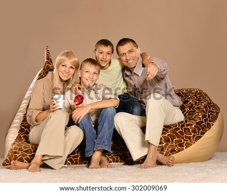 Family at home sitting on brown armchair with tea and apple - stock photo