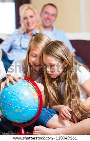 Family at home, the children playing with a globe - stock photo