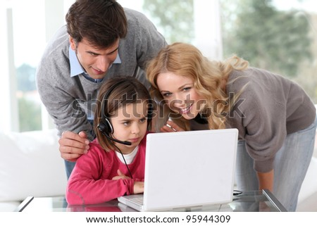 Family at home using computer webcamera - stock photo