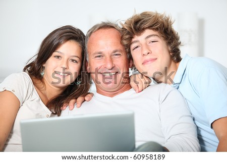 Family at home with laptop computer - stock photo