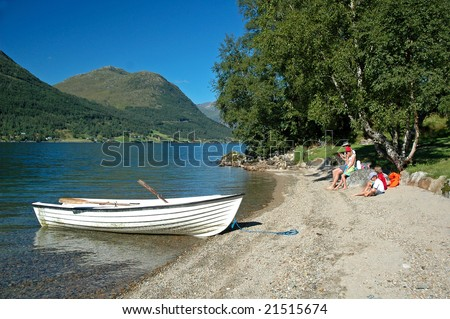 family at lakeside with rowboat - stock photo