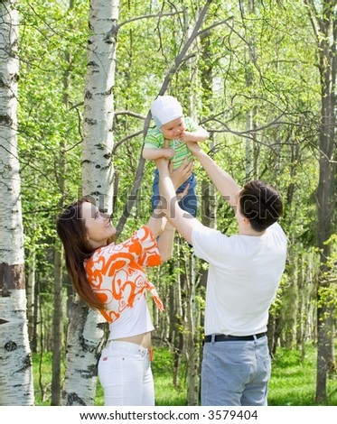 Family at nature. Three persons. Grass. Green forest - stock photo