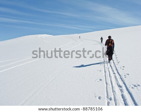 Family at ski climbing up a long slow hillside in the norwegian mountains at easter - stock photo