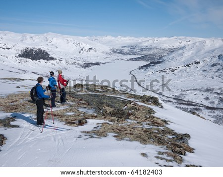 Family at ski standing and resting at a meltet spot in the snow having a panoramic view towards a snow covered lake with mountain summits in the background at winter in norway