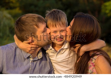 Family at sunset. Parents kissing their kid, child hugging his mother and father.