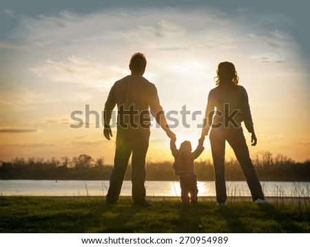 family at sunset standing on the bank of the river - stock photo