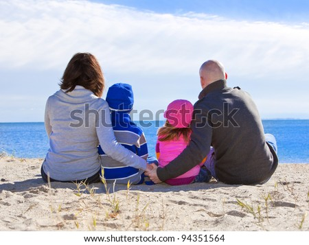 Family at the beach portrait during the winter - stock photo